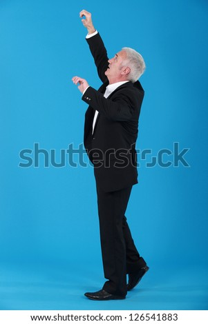 Senior businessman reaching upwards - stock photo