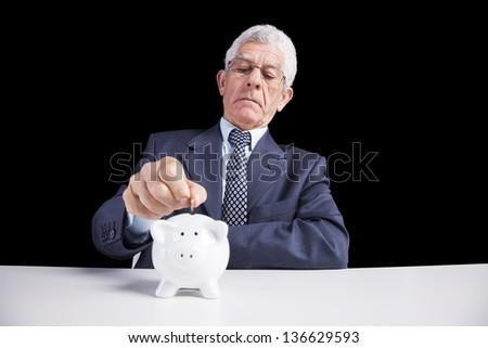 Senior businessman saving some money for his retirement (isolated on black) - stock photo