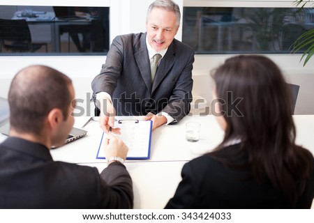 Senior businessman showing a document to sign to a couple - stock photo
