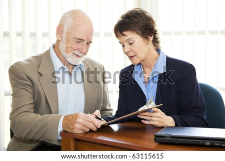 Senior businessman signs a contract with the assistance of a mature businesswoman. - stock photo