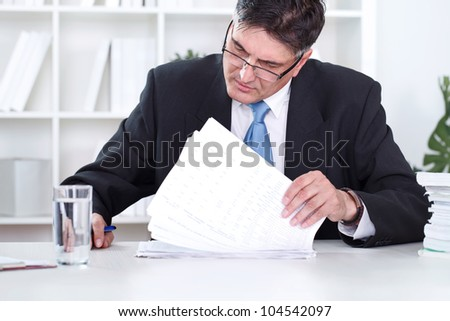 Senior businessman sitting at desk reading documents - stock photo