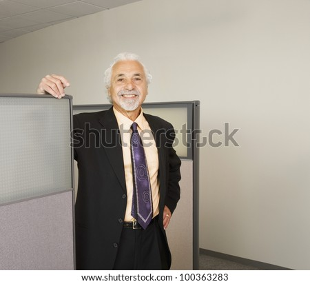 Senior businessman smiling in office cubicle - stock photo