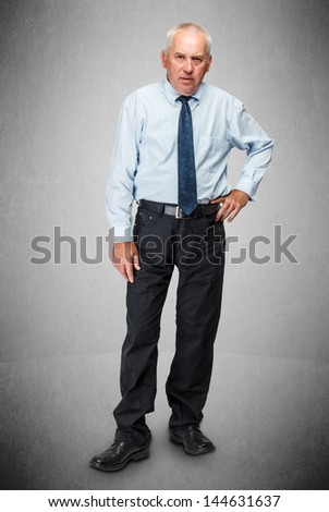 Senior businessman standing on gray background - stock photo