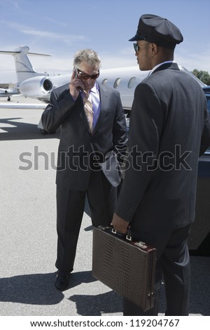 Senior businessman standing outside private jet and talking on phone - stock photo