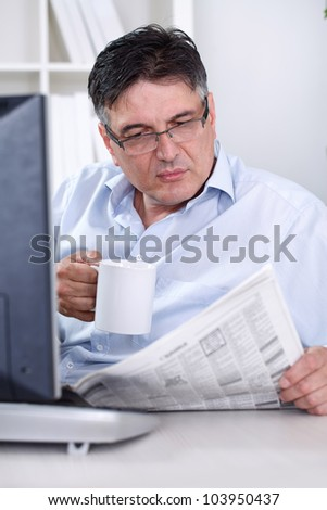 Senior businessman taking break in office, reading newspaper, having coffee, - stock photo