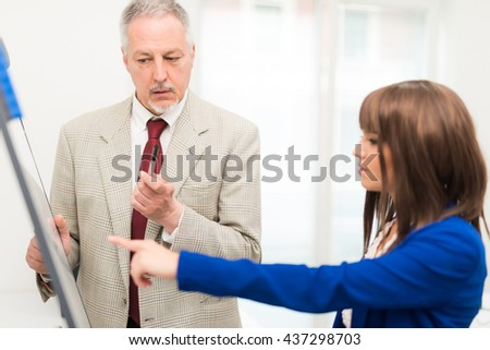 Senior businessman talking to a younger colleague - stock photo