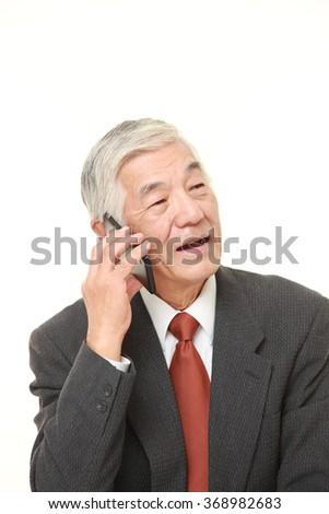 senior businessman talks with a smart phone   - stock photo