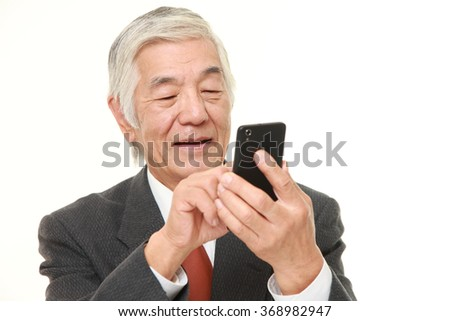 senior businessman texting with a smart phone  - stock photo
