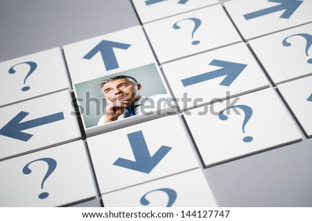 Senior businessman thinking surrounded by question marks and arrows - stock photo