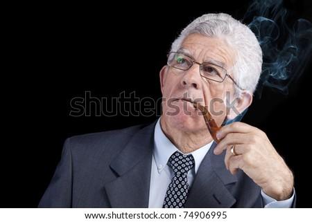 Senior businessman thinking while smoking his pipe (isolated on black) - stock photo