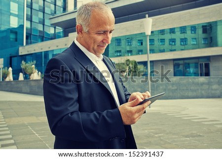 senior businessman using touchpad at outdoor - stock photo