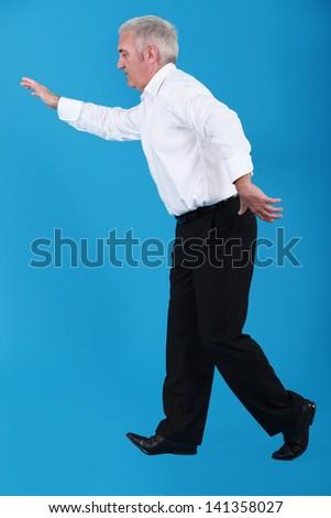 Senior businessman walking along invisible tight-rope - stock photo