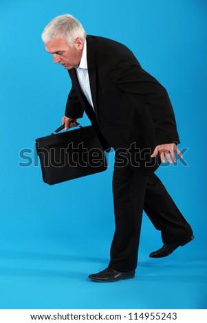 Senior businessman walking invisible tight rope - stock photo