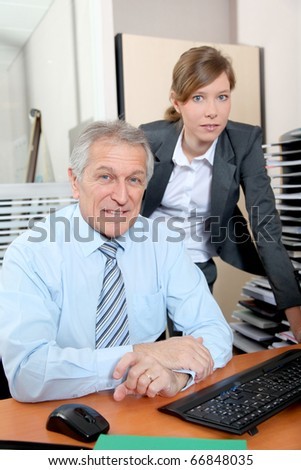 Senior businessman with young woman in the office - stock photo
