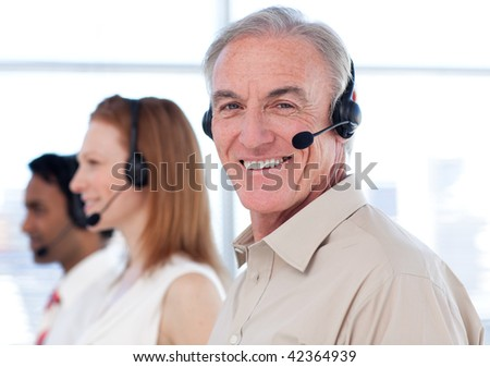 Senior businessman working in a call center with his colleagues - stock photo