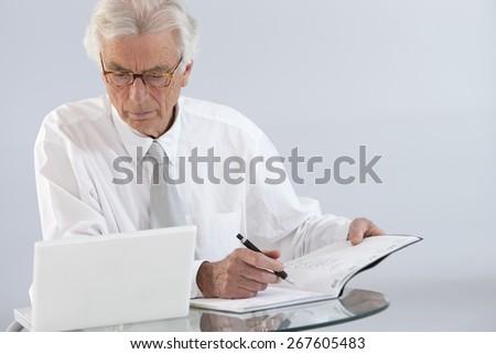 Senior businessman working in office - stock photo