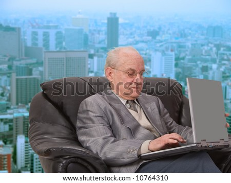 Senior businessman working on his laptop in front of the office window in a big city. - stock photo