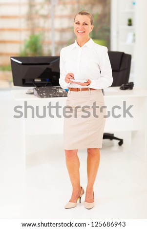 senior businesswoman drinking coffee in office - stock photo