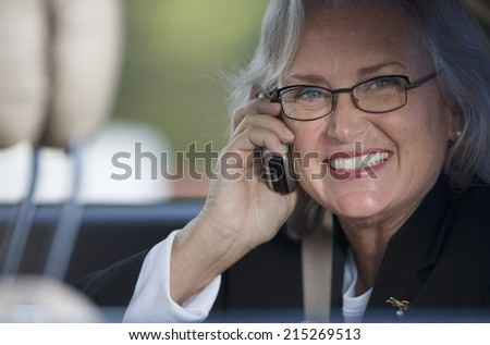 Senior businesswoman in spectacles using mobile phone, smiling, close-up, portrait - stock photo