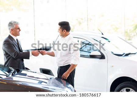 senior car salesman handing over new car key to customer at showroom - stock photo