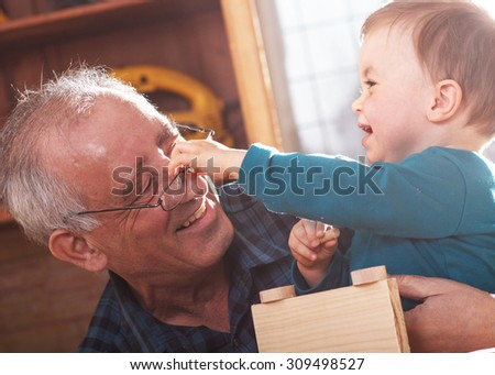 Senior carpenter and his grandson working in the workshop, they make a wooden toy car. - stock photo
