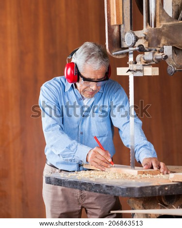 Senior carpenter marking on wood while cutting wood with bandsaw in workshop - stock photo