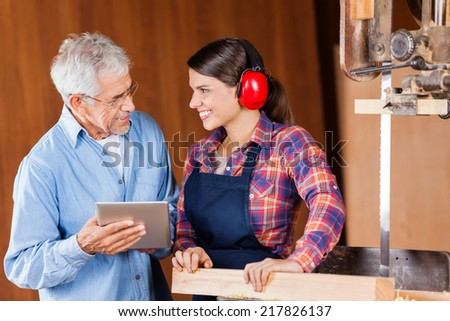 Senior carpenter using digital tablet while looking at female colleague in workshop - stock photo