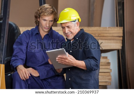 Senior carpenter using digital tablet with colleague in workshop - stock photo