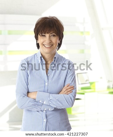 Senior caucasian casual businesswoman standing with arms crossed at bright office. Smiling, looking at camera, copyspace. - stock photo