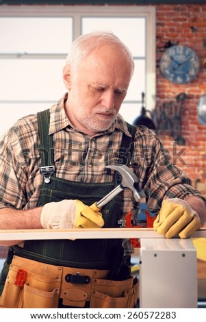 Senior caucasian handyman hammering at DIY home workshop. Working, focused. - stock photo