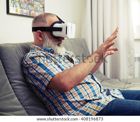 Senior Caucasian man touch something in virtual reality wearing headset glasses - stock photo