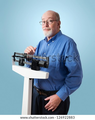 Senior caucasian man weighing himself on vertical weight scale. He looks happy and cheerful. - stock photo