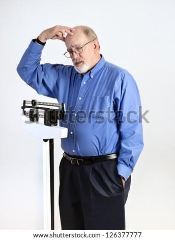 Senior caucasian man weighing himself on vertical weight scale. He looks worried and confused. - stock photo