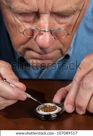 Senior caucasian repairman working on an old pocket watch - stock photo