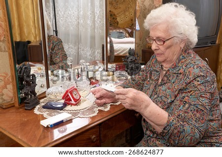 Senior caucasian woman about ninety years old sits near the mirror, takes out pills and reads prescriptions in her bed room - stock photo