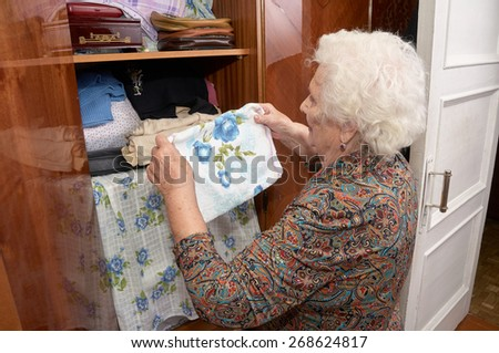 Senior caucasian woman about ninety years old takes towel from the shelf of the wardrobe in her bed room - stock photo