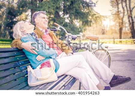 Senior cheerful couple sitting on a bench in a park - Two pensioners having fun together outdoors - stock photo