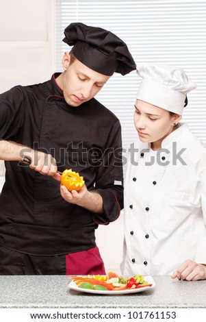 Senior chef teaches young chef to decorate fruit plate in kitchen - stock photo