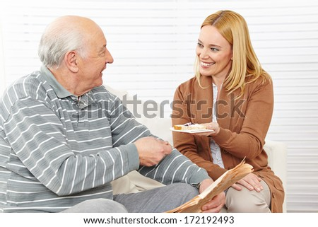 Senior citizen and woman eating breakfast at assisted living home - stock photo