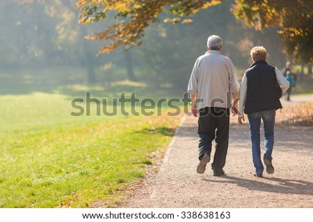 Senior citizen couple taking a walk in a park during autumn morning.  - stock photo