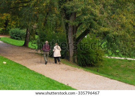 Senior citizen couple walking in the park with nordic walking poles.  - stock photo