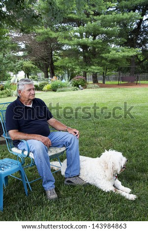 Senior Citizen enjoying the comforts of his home in backyard with his dog sitting next to him - stock photo