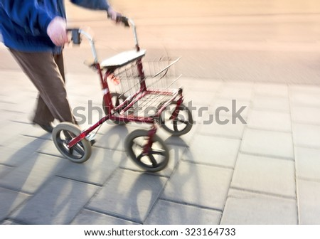 senior citizen with walking frame on sidewalk in blurred motion - stock photo