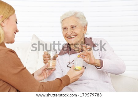 Senior citizen woman getting medical pill with water in a retirement home - stock photo