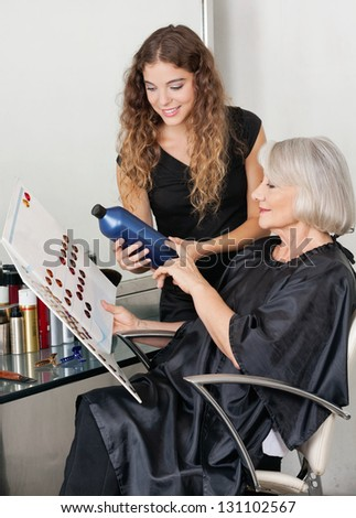 Senior client and hairdresser choosing hair color at beauty salon - stock photo