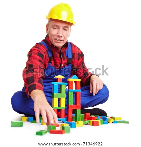 Senior construction worker playing with many colorful bricks - stock photo
