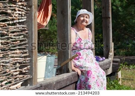 Senior countrywoman sitting on wooden house porch - stock photo