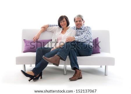 Senior couple affectionately sitting on a white sofa  - stock photo
