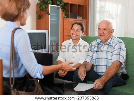 Senior couple answer questions of social worker with notebook in home - stock photo