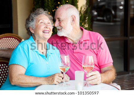 Senior couple at a cafe, enjoying wine and conversation together. - stock photo